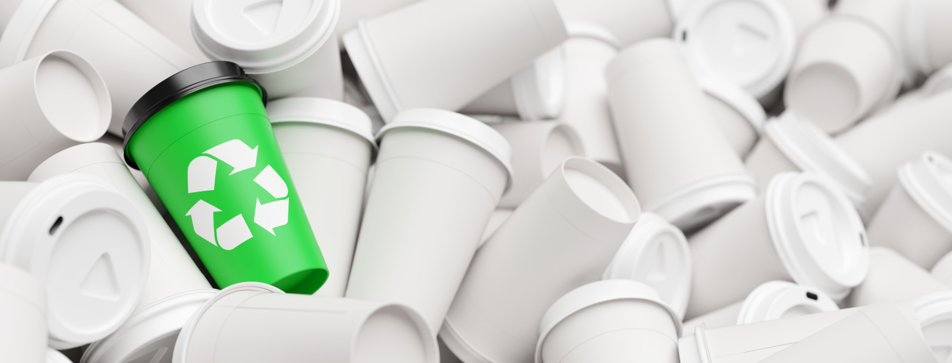 Aus einem Haufen von Abfall Kaffeebechern sticht ein Becher mit einem grünem Recycling Logo heraus