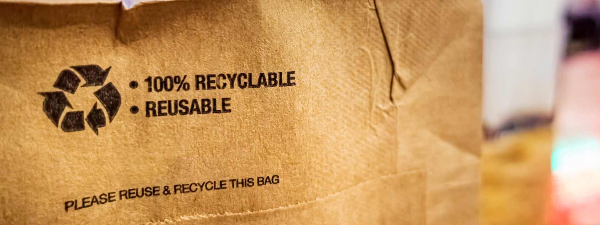 Brown paper bag that is 100% recyclable and reusable on a counter. A printed plea for user to recycle and reuse this bag as a form of packaging.; Shutterstock ID 1506701819; Purchase Order: 20210409; Job: EF HR; Client/Licensee: HR online content